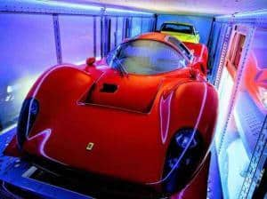 red exotic sports car inside enclosed car carrier