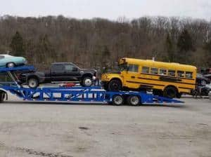 school bus and pickup truck on car transport carrier