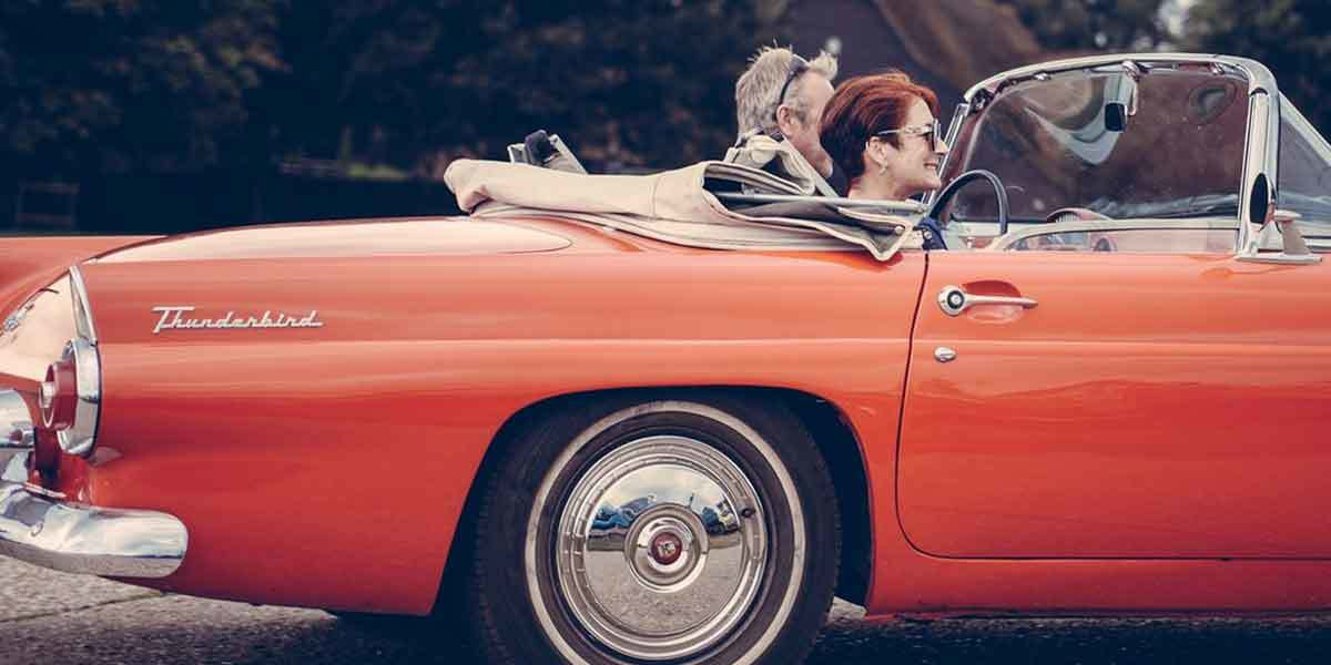 couple in red classic car